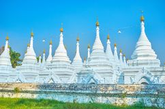 The white stupas of Kuthodaw Pagoda in Mandalay, Myanmar. The rows of white stupas with golden htis of Kuthodaw Pagoda, located on the foor of Mandalay hill royalty free stock photography