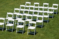 Rows of white wedding chairs. Rows of white empty chairs on a lawn before a wedding or ceremony Royalty Free Stock Photography