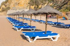 Rows of wicker parasols and beach beds Stock Photos