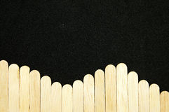 Rows of wooden. The rows wave of wooden sticks with a black background Stock Photo