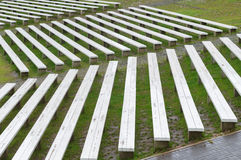 Rows of wooden benches on hillside of outdoor concert area Stock Photo