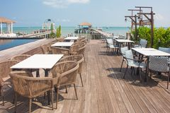 Rows of wooden chair and table locate on terrace of restaurant with seascape in the background. royalty free stock image