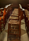 Rows of wooden church chapel chairs with rush seats inside church Royalty Free Stock Photo