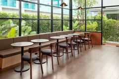Rows of wooden table and chair inside of glass room with garden royalty free stock photography