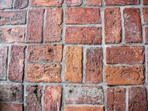 Rows of worn bricks in distinct pattern. Rows of warm red bricks are set in mortar to create a distinct pattern displaying the aged look of the materials Stock Image