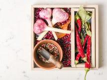 Roxo do alho com pimenta e feijões na caixa de madeira em um fundo de pedra branco Imagem de Stock