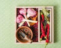 Roxo do alho com pimenta e feijões na caixa de madeira em um fundo de pedra branco Imagens de Stock Royalty Free