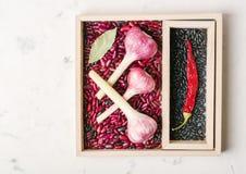 Roxo do alho com pimenta e feijões na caixa de madeira em um fundo de pedra branco Fotografia de Stock Royalty Free