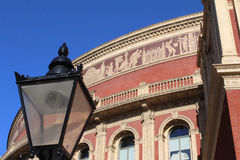 Royal Albert Hall. The Royal Albert Hall in Kensington, London; showing an old lamppost in the foreground and a detail of the frieze along the top Royalty Free Stock Photo