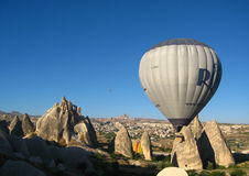 Royal ballons flying in the sunrise light in Cappadocia, Turkey above the Fairy Chimneys rock formation nearby Goreme royalty free stock photo