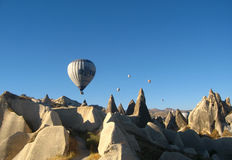 Royal ballons flying in the sunrise light in Cappadocia, Turkey above the Fairy Chimneys rock formation nearby Goreme Royalty Free Stock Image