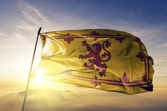 Royal Banner of Scotland flag textile cloth fabric waving on the top sunrise mist fog. Beautiful stock photography