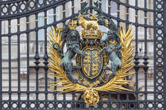 Royal coat of arms at the main Buckingham Palace gate. Golden coat of arms at the main Buckingham Palace gate in London Stock Images
