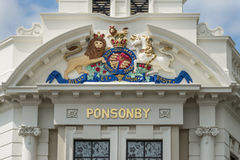 Royal crest on Clocktower mansion on Ponsonby Road, Auckland. Auckland, New Zealand - March 1, 2017: The cream white mansion with clock tower at intersection of stock images
