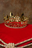 Royal crown on pillow. Medieval golden king's crown on red velvet pillow Stock Image