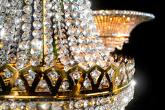 Royal diamond crown chandelier close up. Sparkling shiny golden light Stock Image