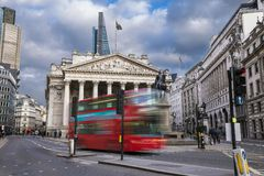 The Royal Echnage building with moving red double decker bus on the move. London, England - The Royal Echnage building with moving red double decker bus on the Royalty Free Stock Image