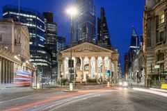 The Royal Exchange in the City of London, United Kingdom. The Royal Exchange in the City of London by night with blurred traffic, United Kingdom stock images