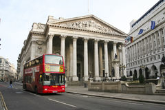 Royal exchange red bus threadneedle street london uk. London, UK - Jan 17, 2009: red 23 bus passing the royal exchange building in the city of london, twice Stock Photography