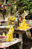 Royal family statuettes in Thailand. Brown and golden statuettes of Thai royal family members outside on wooden table, Buddha statuettes at the background Royalty Free Stock Photo