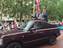 Royal family Windsor. Prince harry kate and will in an open top Range Rover driving down the mall waiving at crowds. Duke and duchess of Cambridge Royalty Free Stock Photography