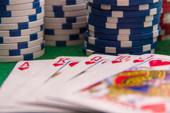 Royal flash. Poker gamble cards on green casino table with chips Royalty Free Stock Photos