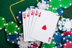 Royal flash on cards and poker chips. On green casino table. success in gambling Stock Photo