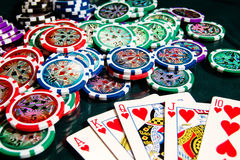 Royal flash win in poker and big heap of poker chips Stock Photos