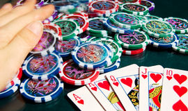 Royal flash win in poker and female hands grabbing bank. Blurred motion. Royalty Free Stock Photography