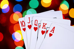 Royal Flush. Playing cards showing a royal flush, over background of colorful defocused lights Royalty Free Stock Image
