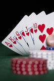 Royal Flush. In focus with red, white and blue poker chips on a green felt surface stock photos