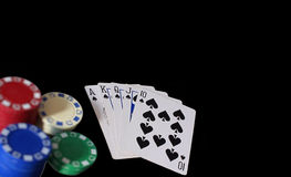 Royal Flush. Playing cards showing royal flush with spades in a game of poker with chips to the side, set on black background stock image