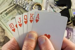 Royal flush. Of playing cards with a money and valuables background Royalty Free Stock Images