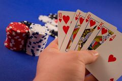 Royal Flush. A hand holding a royal flush with poker chips in the background. Shallow depth of field stock photography