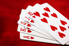 Royal Flush. Heart suit, on vibrant red velvet background Stock Image