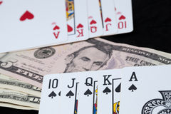 Royal Flush and bank note on black background Stock Photos