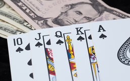 Royal Flush and bank note on black background Royalty Free Stock Photography