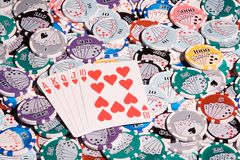 Royal flush on chips. A royal flush of hearts laying on a bed of chips Stock Image