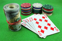 Royal Flush, chips and dollars. On green cloth Royalty Free Stock Photo