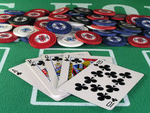 Royal Flush Clubs. Royal flush of clubs in a poker hand on a green felt table top Royalty Free Stock Photos