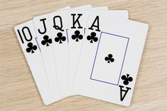 Royal flush clubs - casino playing poker cards. Royal flush clubs - winning hand of gambling casino poker playing cards on a table stock images
