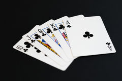 Royal Flush of clubs in poker cards game on a black background Stock Photo