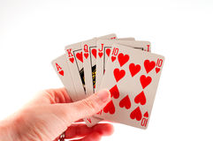 Royal flush. A female hand holding a royal flush of hearts playing cards Royalty Free Stock Photo