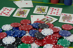 Royal Flush of Hearts. Texas Hold'em royal flush poker hand with a pile and stacks of casino chips Royalty Free Stock Photo