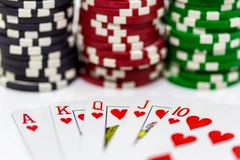 A royal flush of hearts with blurred poker chips in the backgrou. A royal flush with blurred poker chips in the background on a white background Stock Photo