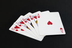 Royal Flush of hearts in poker cards game on a black background.  Royalty Free Stock Images