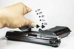 Royal flush playing cards and gun in hand Stock Photo