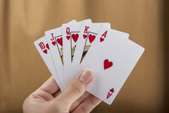 Royal flush. Playing cards in hand isolated on brown background Royalty Free Stock Photos