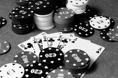 Royal Flush in poker in black and white. Royal flush of shamrocks between betting chips, in black and white Royalty Free Stock Photos