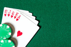 Royal Flush poker card sequence near poker chips. Royal Flush poker card sequence near chips on a green table. Challenge to the casino Stock Photo